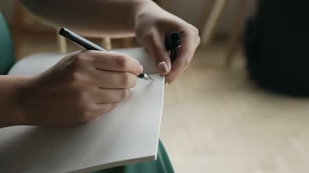em branco : Close-up of a woman writing a hand on an empty notebook with a pen.