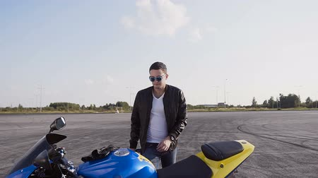 oturur : The biker is dressed in leather jacket and jeans, goes to his motorcycle, sits down on him and wears sunglasses