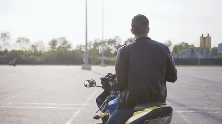 rider : A young biker dressed in a black leather jacket and blue jeans with a helmet in his hands goes to his motorcycle Stock Footage