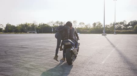 bikers : The girl in a leather jacket with a leather backpack on her shoulders, approaches the motorcycle where her boyfriend is waiting and they together to ride around the city on the motorcycle