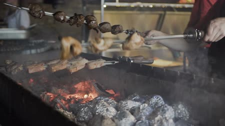 biber : Barbecue. Marinated barbecue is cooked on a brazier with potatoes which is wrapped in foil on charcoal. Baked potatoes on charcoal Stok Video