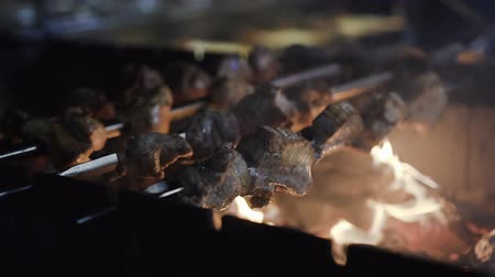 barbecued : Grilled shish kebab on metal skewer.with lots of smoke. BBQ fresh beef chop slices. Flame from griil