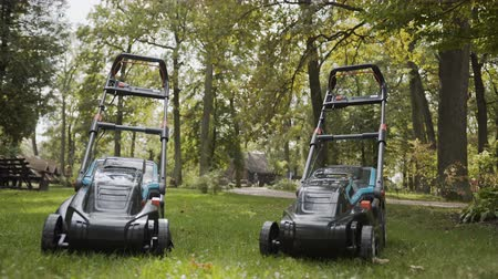 benzine : Two lawn mowers are in the park on the grass