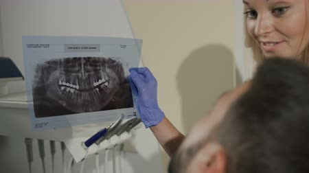 professionalism : The dentist-woman shows the patient an x-ray for further treatment of the teeth. Dentistry. Dentist shows a young mans ill tooth on a radiograph Stock Footage
