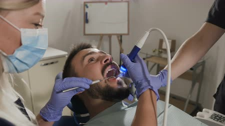 brackets : Patient having dental treatment at dentists office. Man visiting her dentist Stock Footage