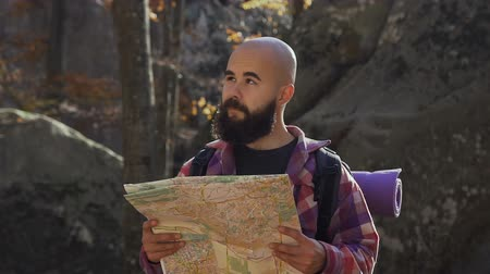bald mountain : Stylish hipster man traveler with backpack holding map and exploring on top of mountains, travel concept Stock Footage