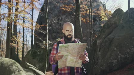 bald mountain : A wonderful hipter wearing a beard, standing high in the mountains and holding a tourist card in his hands. Autumn tourism concept
