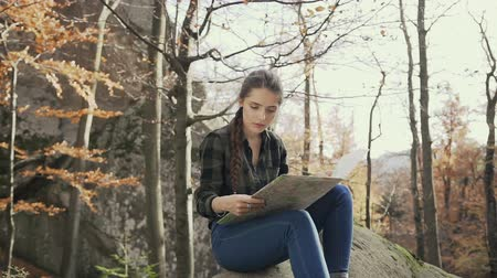 ansiklopedi : Beautiful young girl with long hair braided in a braid, sitting on a rock in the woods and looking at the map. Golden autumn Stok Video