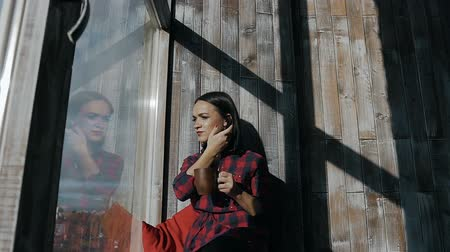 oturur : Beautiful young girl sits on a sunny winter day at the window and holds in her hands a hot cup of tea Stok Video