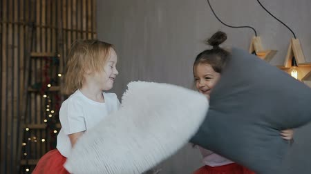 ágynemű : Close-up.Two young girls. Two little sister - brunette and blonde jump on the bed and have fun playing soft pillows. Happy children are twins