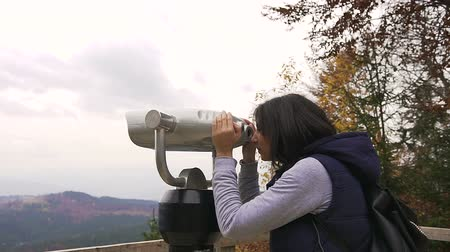 görüş uzaklığı : Girl viewing horizon. Hipster young girl with dark backpack looking on observation deck. Side view of traveler tourist woman who looking at binoculars on the mountains, coin operated binoculars