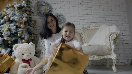 плюшевый мишка : A young woman with a small child sits on a floor near a Christmas tree in a bright spacious room and rejoice in gifts in golden boxes. White the toy bear sits on the floor near the Christmas tree