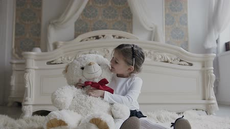 младенчество : Beautiful little girl sitting on a soft carpet in the bedroom with a large toy soft bear