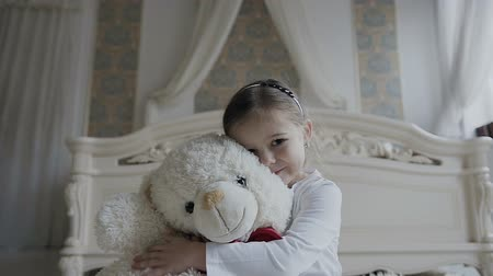 curioso : Little girl sits on a white carpet at the bed and hugs a soft, bear toy. Beautiful girl and her white soft toy bear