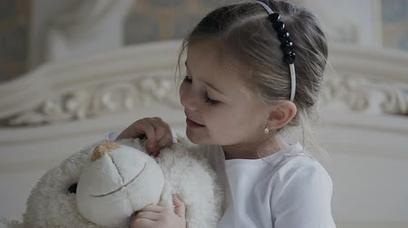 knitted gloves : Close-up. Little girl sits on a white carpet at the bed and hugs a soft bear toy. Beautiful girl and her white soft toy bear