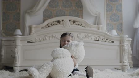 amor : A charming girl sits on the floor at the bedside and joyfully plays with soft teddy bear. Cheerful baby and her teddy bear is a soft, white toy