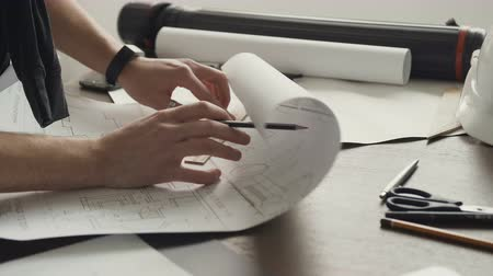 táblázatkezelő : A young male architect is working on the project of new apartments. Husband is an architect draws a plan, graphic, design, geometric figures with a pencil on a large sheet of paper on the office desk Stock mozgókép