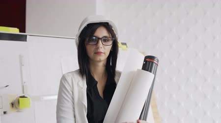 Close-up. A white helmet hat and projects on paper in the hands of a woman architect. A young woman is an architect in a white protective helmet and glasses
