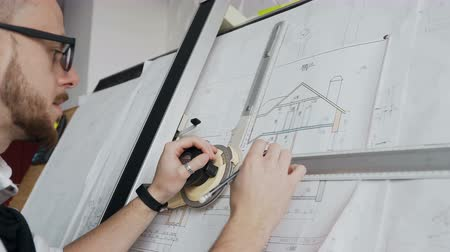 архитектор : A close-up of a male architect who has a beard and glasses is working on a project of a residential building Стоковые видеозаписи