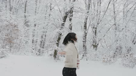 Beautiful young girl with dark hair in a knitted sweater with a scarf and knitted mittens walks in the winter forest during snowfall