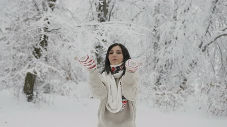 Beautiful young girl dressed in a wool sweater and a warm scarf catching snowflakes with her warm knitted mittens in a snowy forest. A woman blows snowflakes out of her mittens