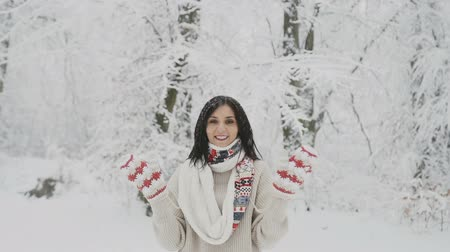 A smiling young woman with dark hair in a woolen sweater and a warm scarf is in a snow-covered forest and in woven mittens waving her hands hello 動画素材