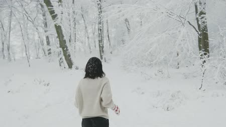 Young brunette girl in a warm sweater with gloves and a scarf joyfully runs up in a snowy forest during a little snowfall