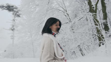Close-up of a young brunette woman who looks into the camera on a frosty winter day and who walks in a snow-covered forest in a stylish wool sweater, warm scarf and knitted mittens