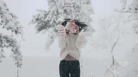 Brunette woman on vacation throwing snow in air in forest with a nice smile. Cute girl wear red with white scarf and knitted mittens , and stylish sweater. Good weather and snowfall.