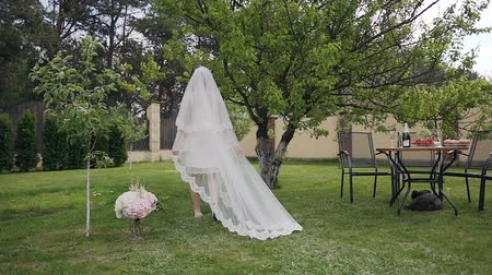 Beautiful blonde bride in a luxurious long wedding dress walking in green garden. Morning of the bride. Wedding day 動画素材
