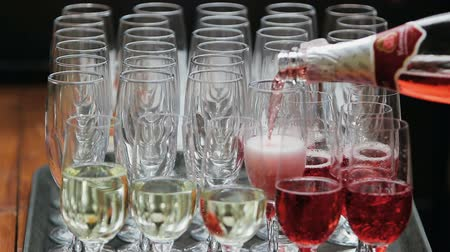 Close-up sparkling on champagne. A red champagne is poured into a glass from a bottle. White and red sparkling champagne