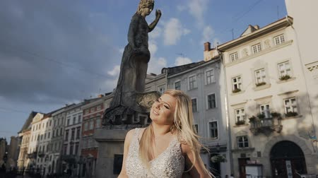 Beautiful young blonde girl with long hair standing at the east sunset in the old town. Sunny day of summer morning