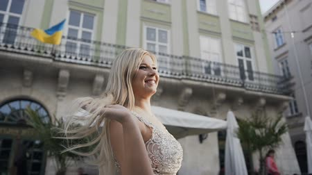 A beautiful model stands in the city, fixes her long white hair and her looking in the distance. The old Town Стоковые видеозаписи