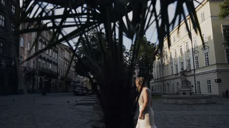 A charming young girl in a white long dress with long white hair walks in the morning to an old city in the east. The concept of summer Stockvideo