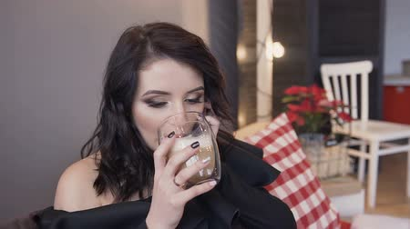 Close-up of a beautiful young brunette girl with a wonderful make-up and a hair style that fun is talking on the phone and drinking hot coffee with milk Стоковые видеозаписи