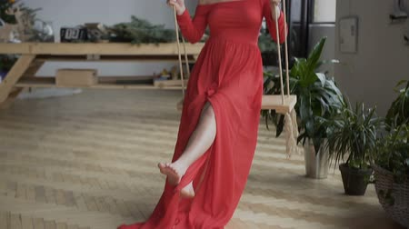 kostka : Beautiful and sexy pregnancy woman in a red dress with dark hair of sitting on a swing and swinging