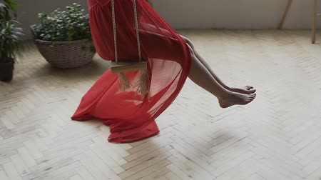 Young pregnant woman swinging on a wooden swing. A young girl in a long red dress on a swing in the studio Стоковые видеозаписи