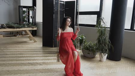 Beautiful pregnant woman in a long red dress swinging on the swing in a stylish studio with large windows Stockvideo