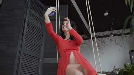 expectativa : Young pregnant woman shows her belly via online social networks, using free wifi in the phone while having rest on the swing in the apartment Vídeos