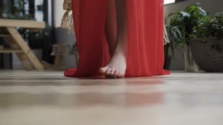 Close up.The girl in red dress goes barefoot on the floor on the camera Стоковые видеозаписи