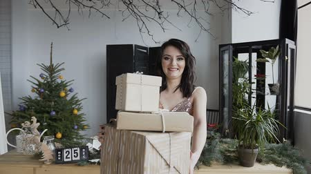 oldalt : A pregnant woman in an evening dress with a wonderful makeover holds boxes in which packed Christmas gifts. The concept of winter. New Year. Christmas holidays Stock mozgókép
