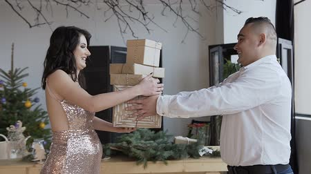 A man gives presents to his beautiful pregnant wife. Happy pregnant wife Conception of pregnancy, Christmas holidays, gifts in boxes, family