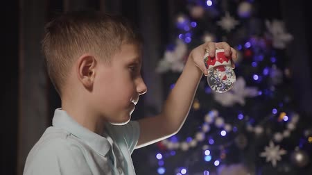 enjoyable : Close up. On a Christmas party, a little boy is playing with a snow globe inside which is santa Stock Footage