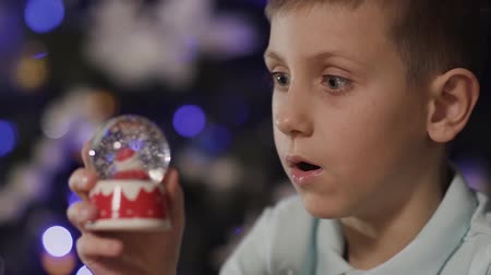 santaclaus : Close-up The boy holds in his hands a snow globe, in the middle of which there is a santa, and astonishedly shakes it. Christmas tree, toy, holiday Stock Footage