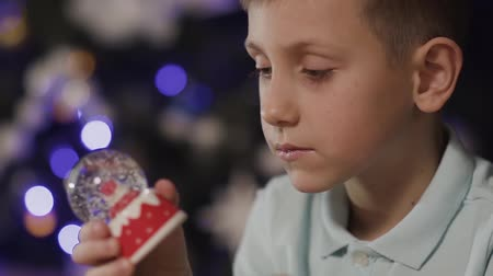 santaclaus : Close-up On the background of a blurred Christmas tree, the boy shakes a decorative toy ball in the middle of which is the Santa Clause Stock Footage