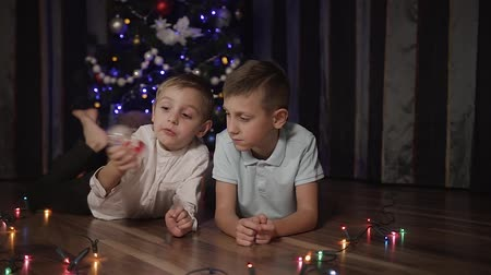 statuette : Two young guys are lying on the floor in front of a Christmas tree and are playing with a snow globe inside which is a Santa Claus