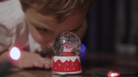 x mas : Close-up of a little boy who looked curiously at the smudged snow globe inside shoved which is a Santa Claus Stock Footage