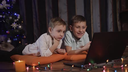 almofadas : Two beautiful little guys are lying on orange decorative pillows on the floor in the living room and watching a cartoon on a laptop through a social network. On the floor in front of the children laid out colored garlands that glow