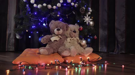 cicili bicili : Ride a camera on two toy teddy bears sitting on orange pillows near a Christmas decoration tree. Christmas decor, apartment, soft toys, luminous garlands