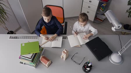 písanka : Two students do homework at home. The guys draw designs for houses that are on their table. Two junior schoolboys doing lessons at home Dostupné videozáznamy